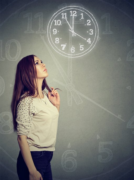Young casual woman looking up in thoughts at clock on gray background