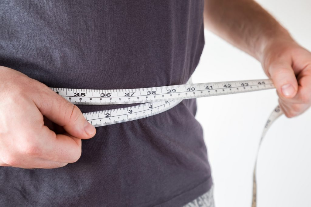 man measuring waist line