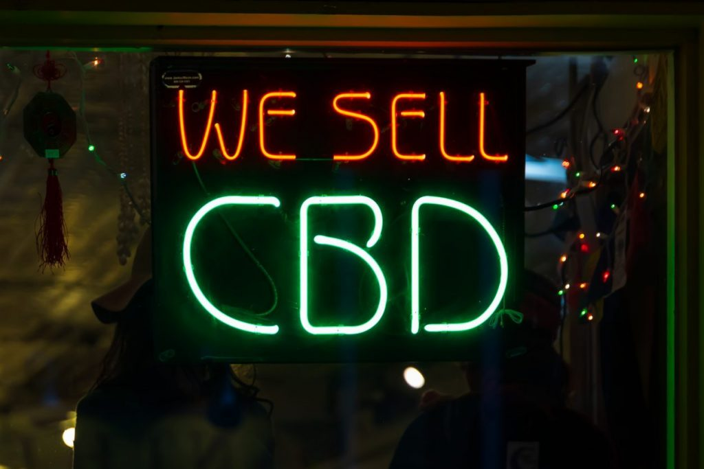 Asheville, NC, USA-2/16/19: A store advertises cannabidiol with red and green neon signs.