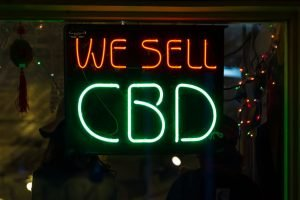 a neon sign saying we sell cbd oil inside a storefront window