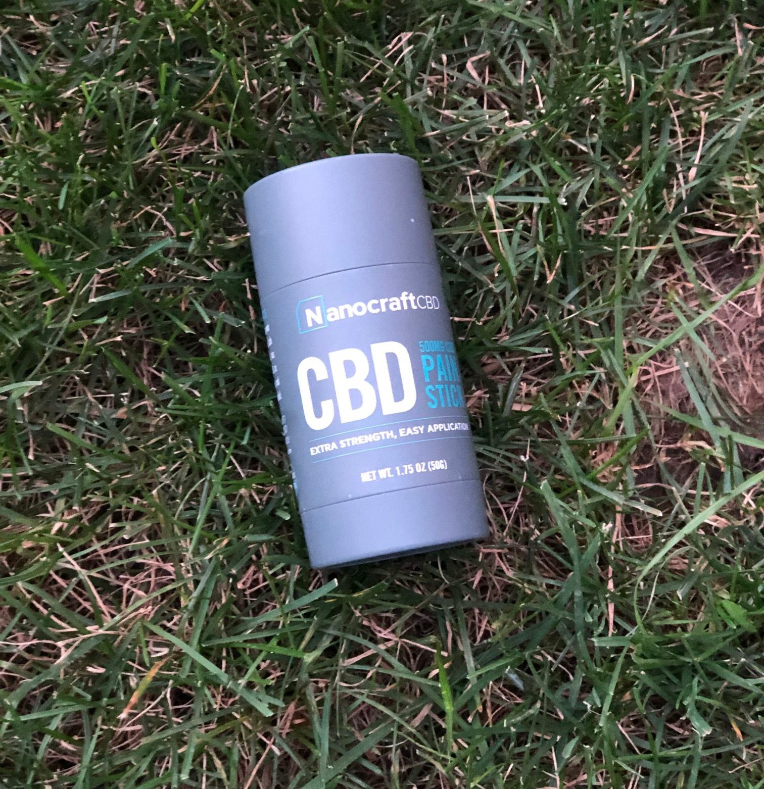 nanocraft cbd pain stick placed on green grass
