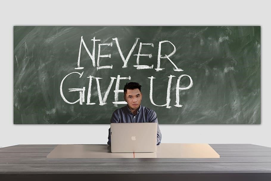 man on a laptop with the words, never give up written on blackboard behind him