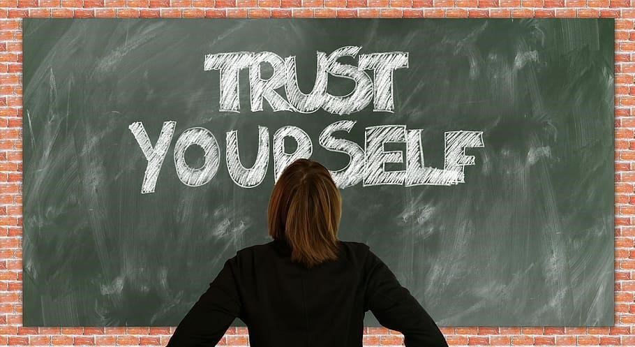 woman looking at blackboard that has the words trust yourself written on it