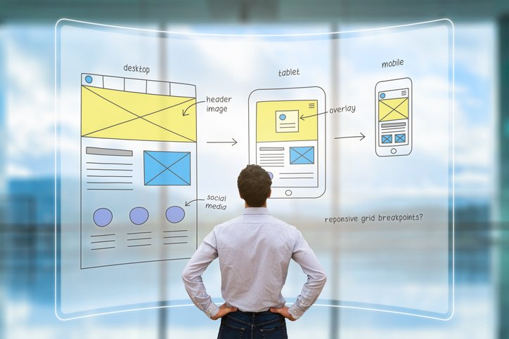 Website development UI/UX front end designer reviewing sketched wireframe layout design mockup for responsive web content with AR screen