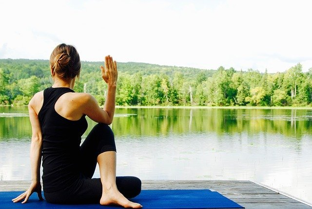 woman doing yoga on a dock overlooking the lake