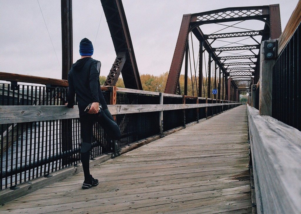 man stretching his leg before going for a run across a bridge