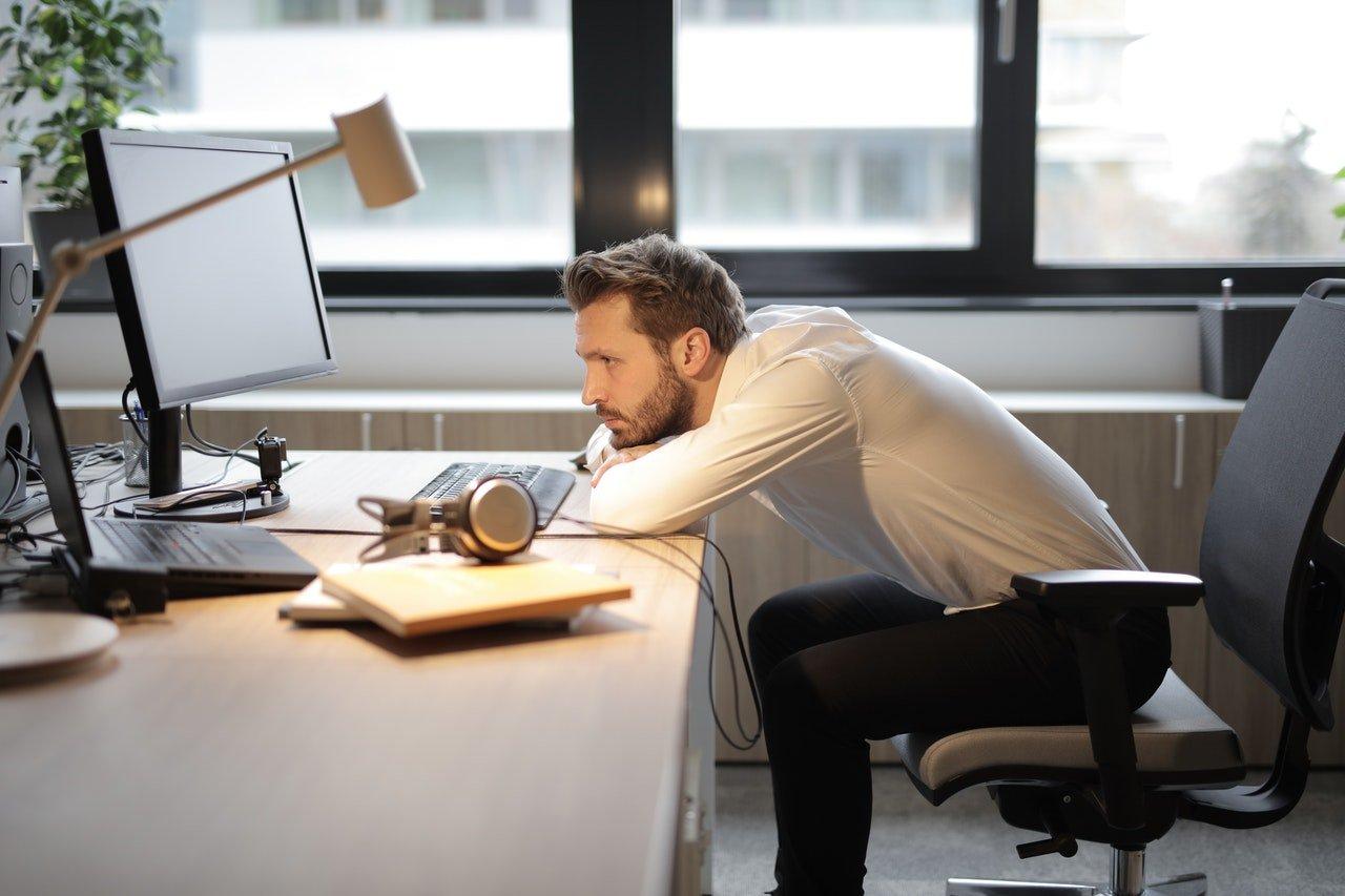 man-tired-at-desk-at-work